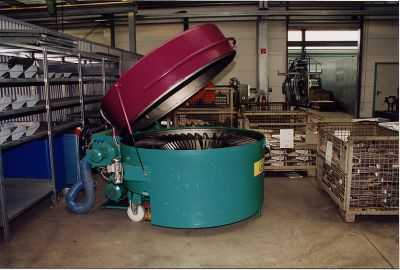 Cleaning machine as moveable top loader. Positioned close to the drawing press for the construction of seat consoles.